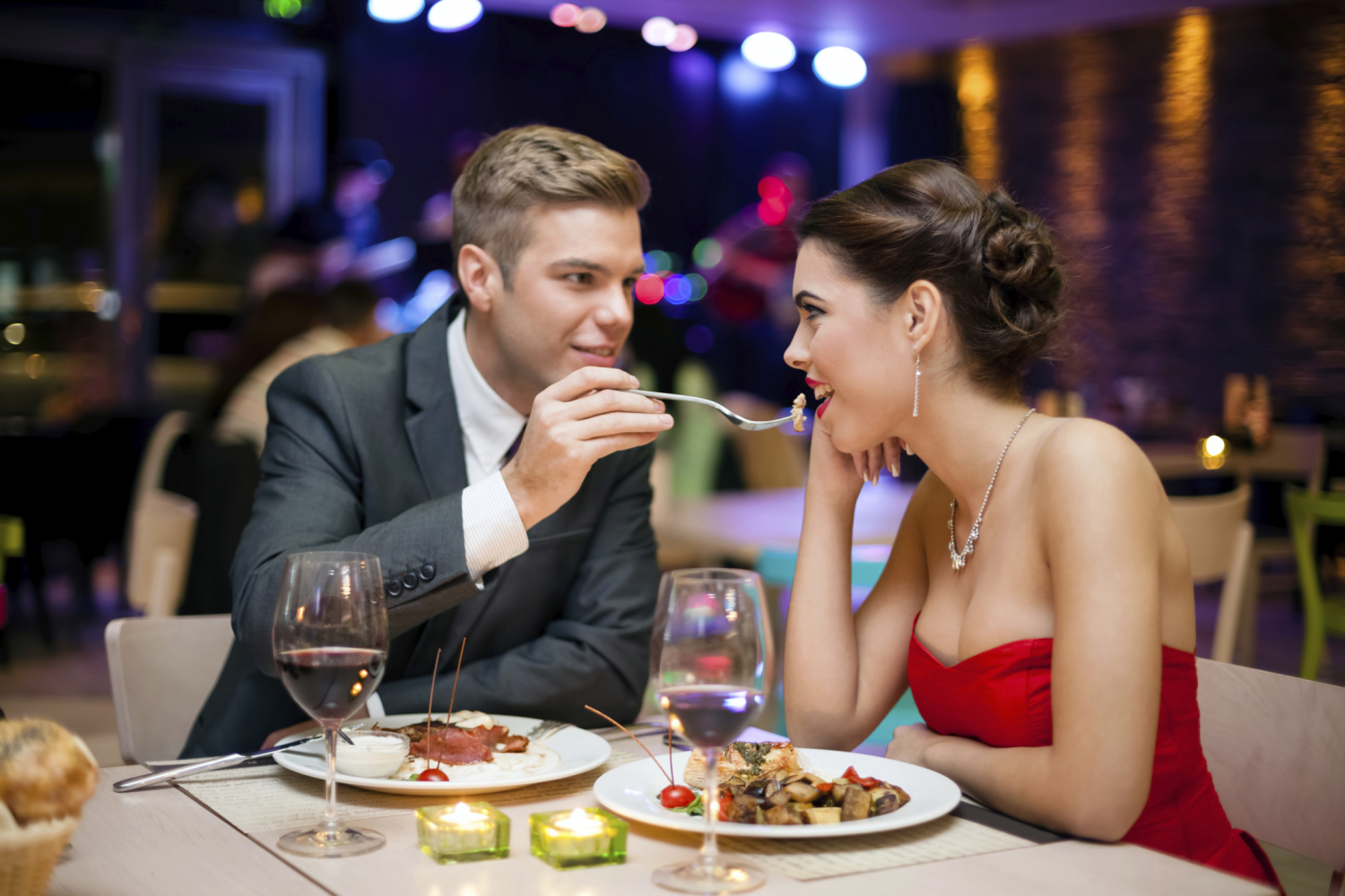 A man and a woman sitting at a table eating food