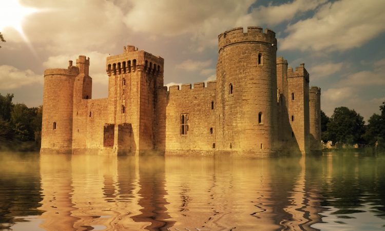 A castle surrounded by a body of water with Bodiam Castle in the background